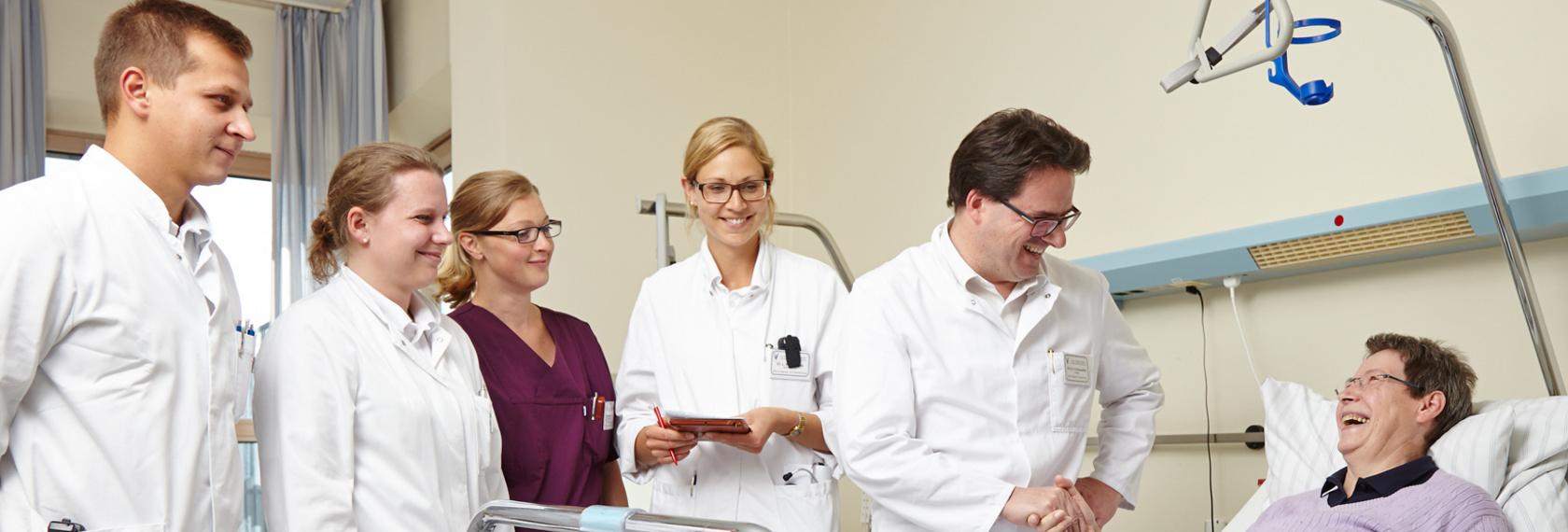 Ein Team aus Ärzten und Pflegepersonal führt die Visite in einem Patientenzimmer durch